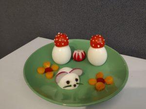 Na zielonym talerzu znajdują się ugotowane jajka w pozycji pionowej z kapeluszem zrobionym z małego pomidorka w białe kropki zrobione z jogurtu. Jedno jajko jest przecięte na pół i położone żółtkiem do strony talerza. Plasterek rzodkiewki jest przecięty na pół i każda z tych połówek osadzona jest na końcówce jajka tworząc uszy. Poniżej rzodkiewek znajdują się oczy zrobione z dwóch ziarenek pieprzu. Poniżej oczu są wąsy zrobione z zielonego szczypiorku.
