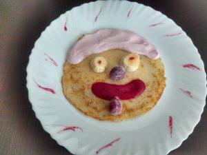 Na białym talerzu jest naleśnik ozdobiony jogurtem owocowym i musem malinowym oraz owocami. Ozdoba ma wygląd uśmiechniętej buźki.