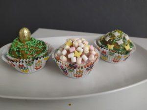 Na białym talerzu widnieją trzy upieczone babeczki. Pierwsza ozdobiona jest zielonymi kuleczkami z lukru, a w środek babeczki wbite jest złote ozdobne jajeczko. Druga babeczka ozdobiona jest biało-żółto-różowymi piankami. Trzecia babeczka ozdobiona jest żółto-biało-zielonymi kuleczkami oraz białymi i żółtymi lukrowanymi motylkami.