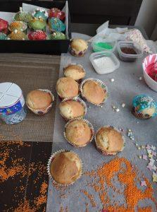 Na szarym blacie kuchennym znajdują się upieczone babeczki. Wokół nich przygotowane są produkty do dekoracji typu lukier, kolorowa posypka, ozdobne gwiazdki.