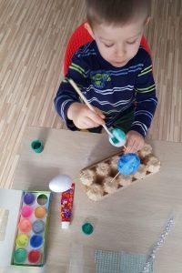 Kilkuletni chłopiec siedzi przy stole i maluje pędzlem jajka styropianowe na patyczkach. Na stole leżą przygotowane farby, klej, ozdoby.