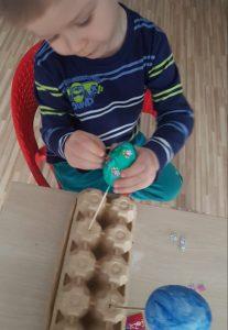 Kilkuletni chłopiec siedzi przy stole i ozdabia jajka styropianowe przyklejając ozdoby.