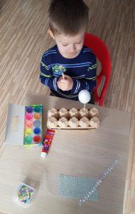 Kilkuletni chłopiec siedzi przy stole i trzyma w dłoniach pędzel. Na stole leżą przygotowane farby, klej, ozdoby, jajko styropianowe na patyczku.